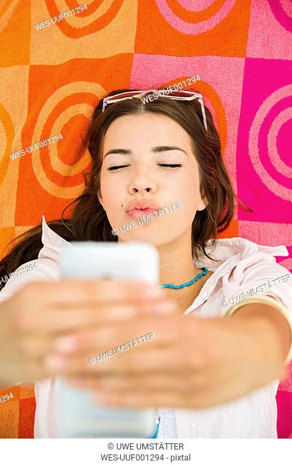 Portrait of young woman lying on beach towel taking a selfie, elevated view