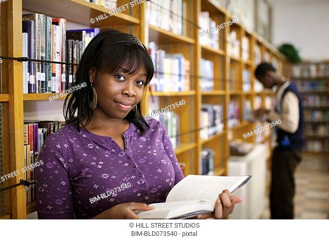 African teenage girl reading in school library