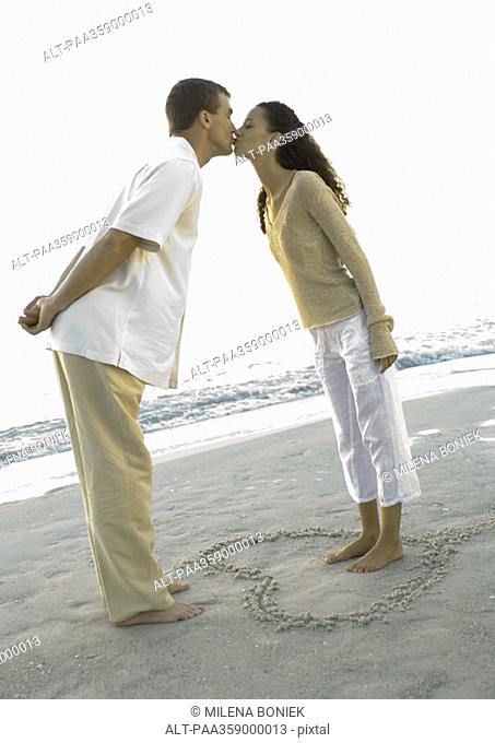 Newlyweds, woman standing inside heart drawn in sand, leaning forward to kiss husband