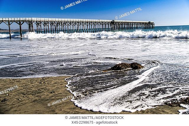 Waves wash ashore beside the old pier at San Simeon in California