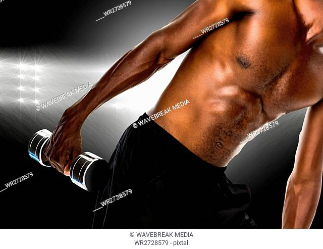 Man performing exercise with dumbbell against black background