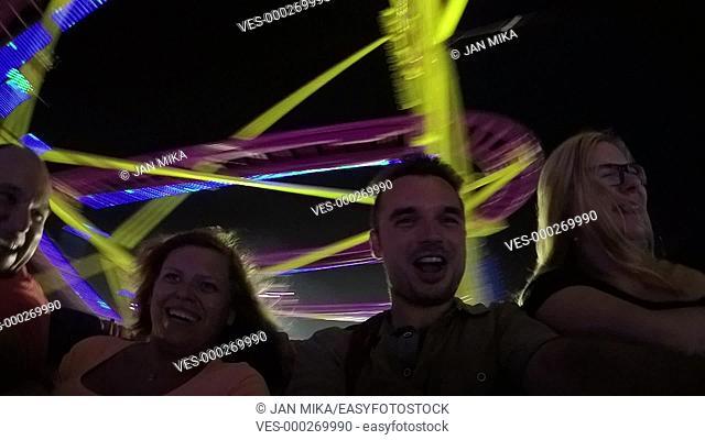 Happy people enjoying roller coaster ride in amusement park at night