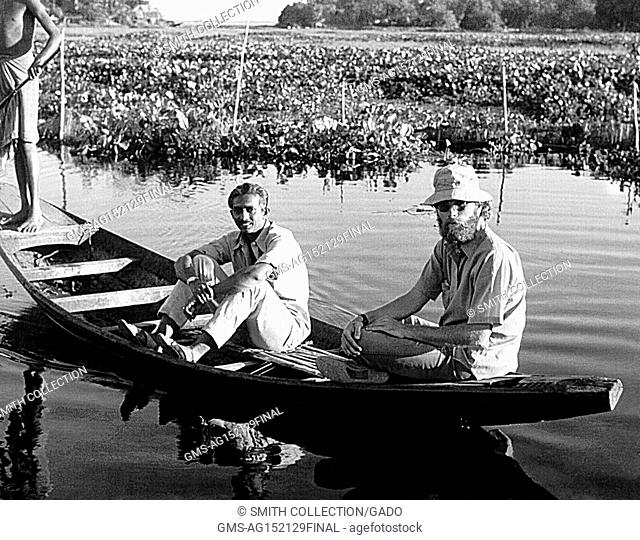 Jeff Koplan, MD MPH with another man and a native villager in a small boat among marshland during a smallpox eradication effort, Bangladesh, 1970