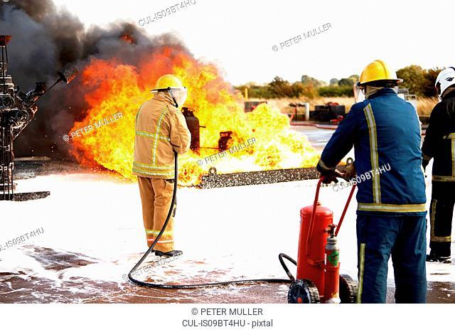 Firemen training, team of firemen spraying firefighting foam on fire at training facility, rear view