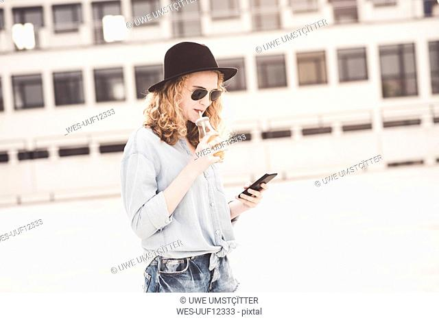 Young woman drinking beverage while using cell phone