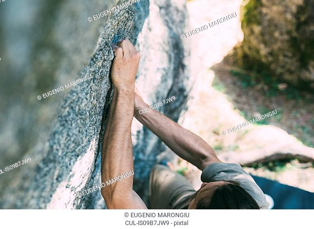 High angle view of young male boulderer gripping boulder, Lombardy, Italy