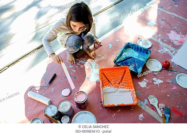 Girl in garage stirring paint in paint tins