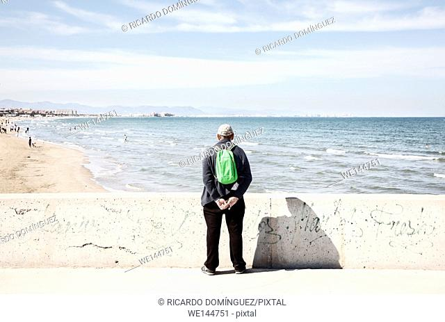 Man watching the Arenas beach and the sea. Valencia, Spain