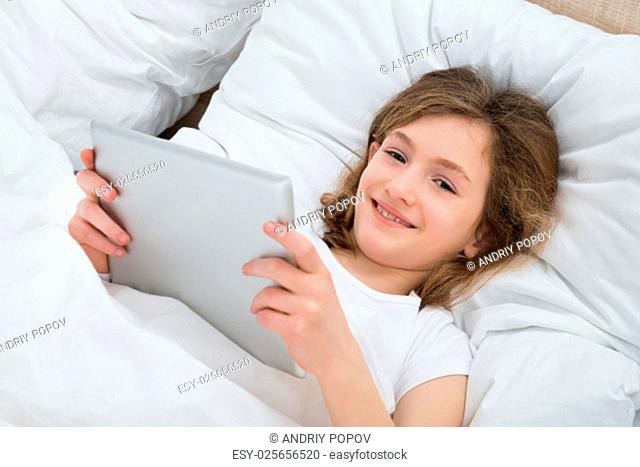 Happy Girl With Digital Tablet Lying On Bed