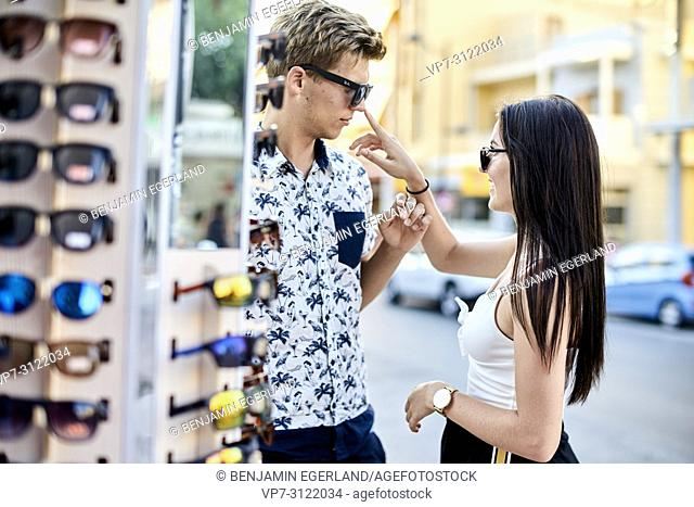 Couple choosing sunglasses at shop. Chersonissos, Crete, Greece