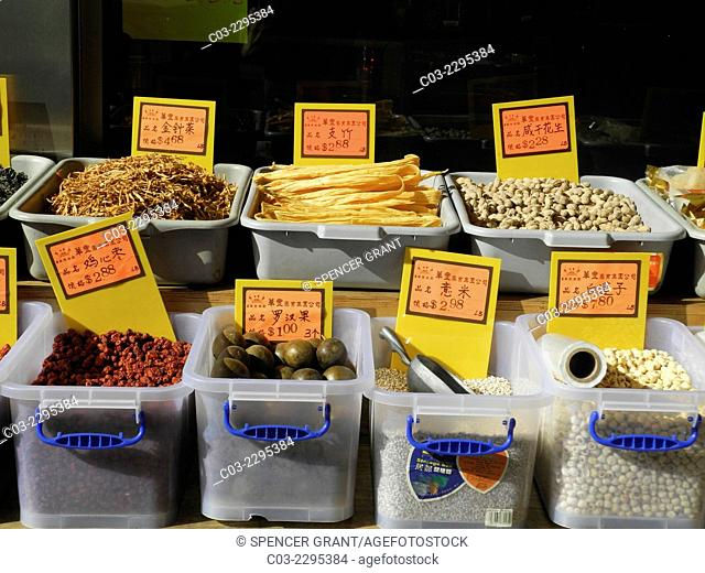 Chinese food items on sale displayed in sidewalk bins in afternoon sun in New York City's Chinatown. Note labels in Chinese only