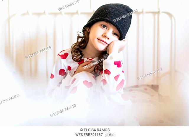 Portrait of little girl sitting in bed wearing cap and pyjama