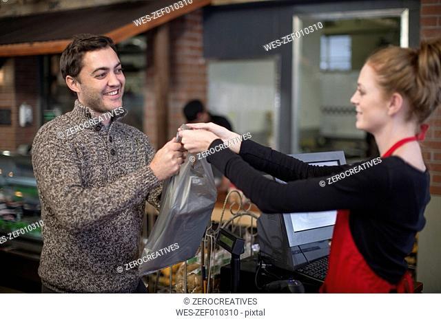 Shop assistant handing over bag to customer in shop