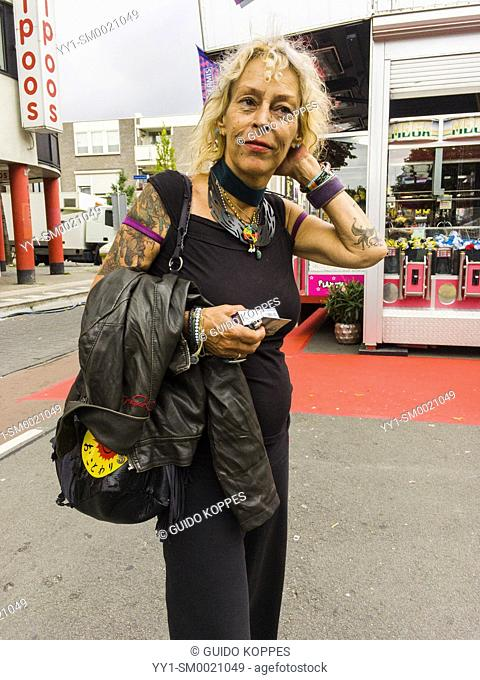 Tilburg, Netherlands. Mature adult caucasian woman with tattoo's trolling the annual fairgrounds