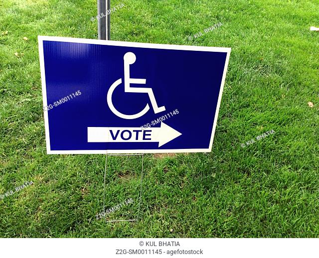 A wheel chair symbol points in the direction of the voting station, Ontario, Canada