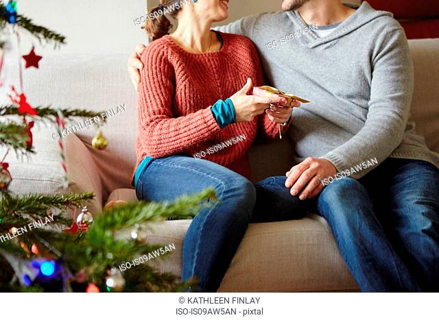 Couple handing xmas gifts on living room sofa