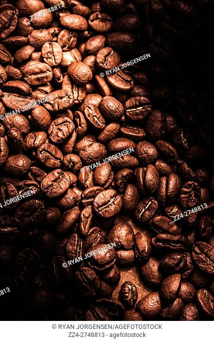 Beverage foods still life composed of a mound made with coffee beans with highlighted centre in darkness