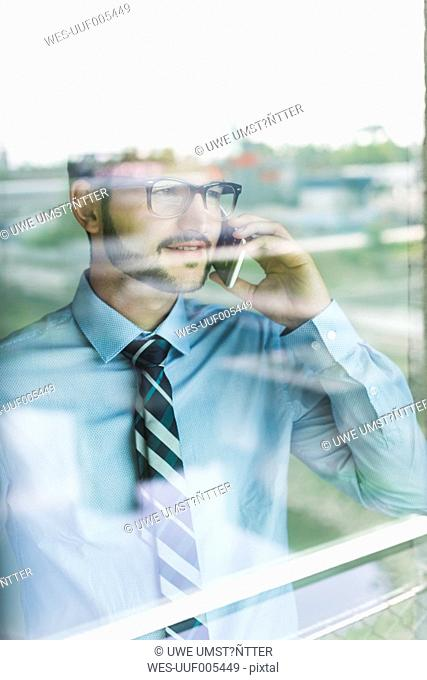 Young businessman on cell phone behind windowpane