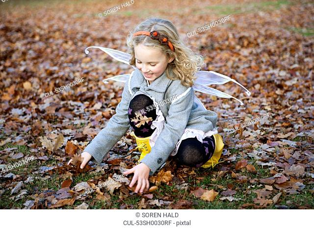 Girl in fairy wings playing in leaves