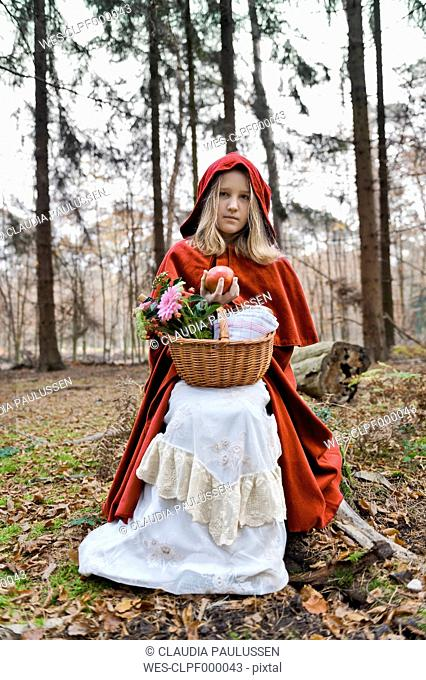 Girl masquerade as Red Riding Hood sitting on a trunk in the wood