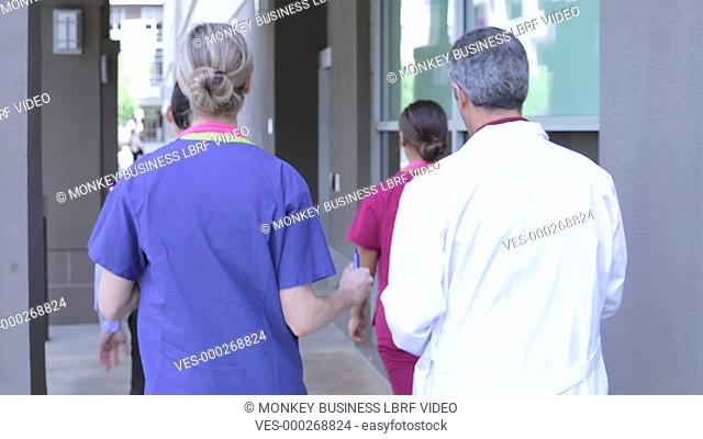 Rear view as four members of medical walk into hospital whilst having discussion.Shot on Sony FS700 in PAL format at a frame rate of 25fps