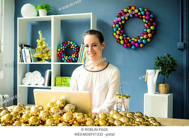Portrait of smiling woman sitting at table with laptop and many golden Christmas baubles