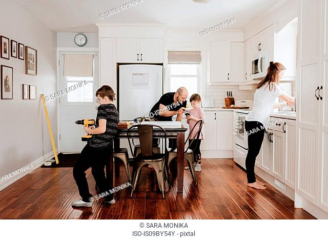 Family of four busy with chores in kitchen