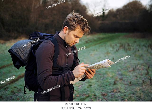 Male hiker reading map in field