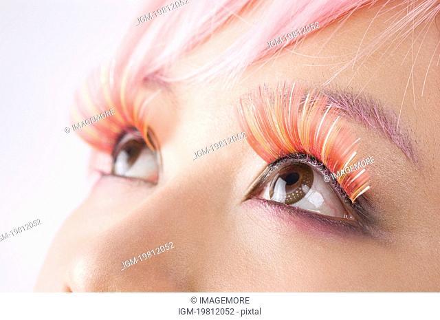 Close up of a young women's wearing long false pink eyelashes