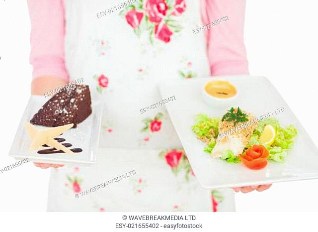 Maid holding plates of healthy meal and pastry