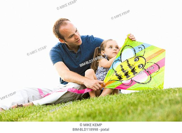 Caucasian father and daughter fixing kite in grass