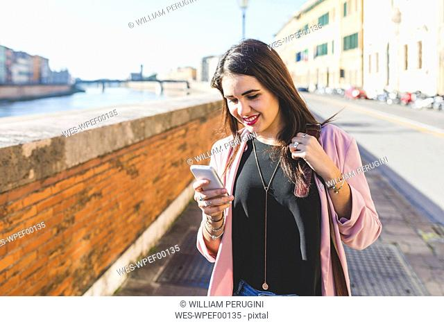 Young businesswoman with her smartphone in the city