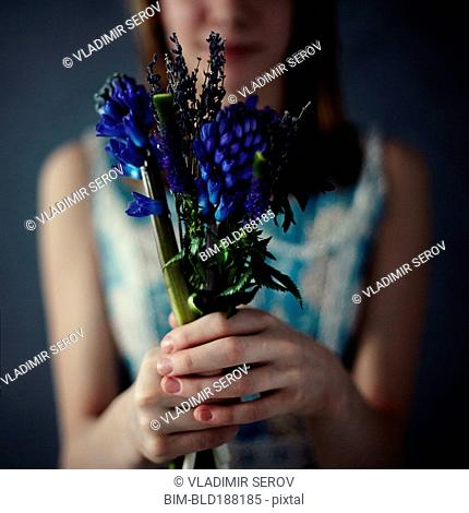 Caucasian teenage girl holding bouquet of flowers