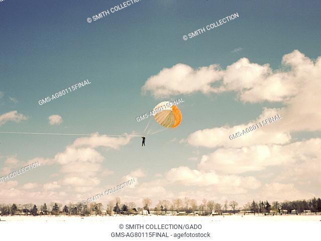 Man parasailing behind a snow mobile, 1970