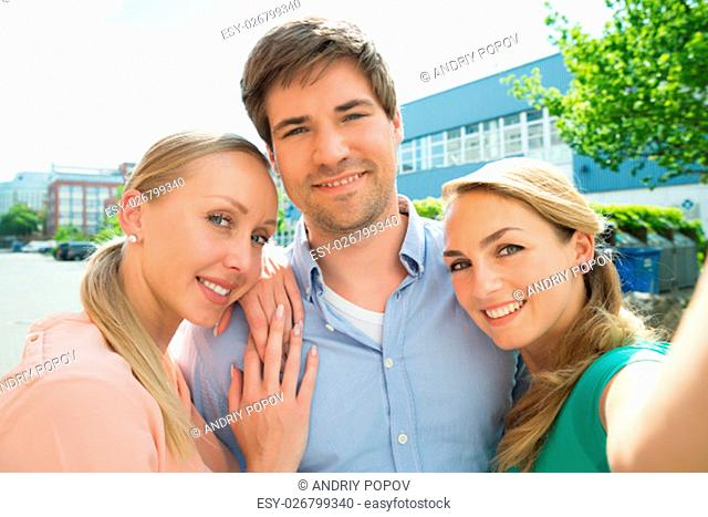 Group Of Young Happy Male And Female Friends Taking Selfie
