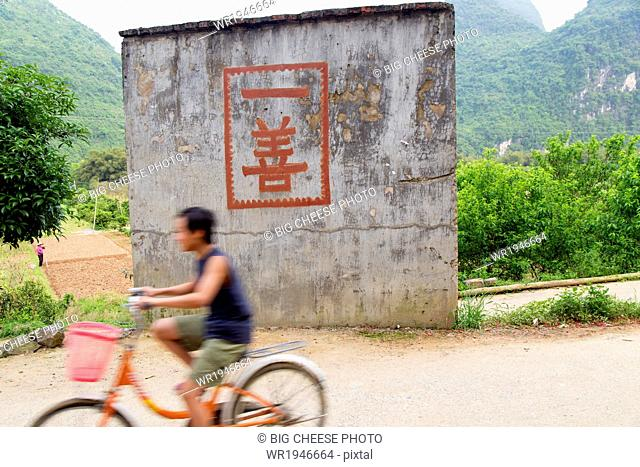 Boy rides a bicycle past a one good deed sign in the countryside, Yangshuo, China