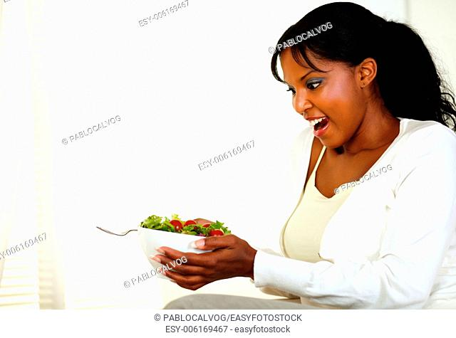 Portrait of a surprised beautiful woman holding and looking to a green salad bowl on light background. With copyspace