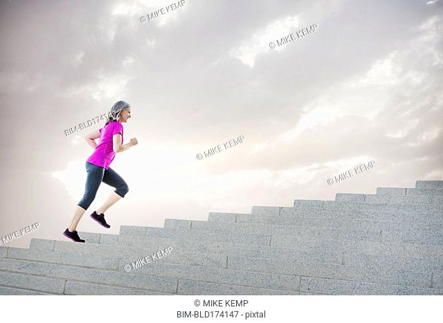 Caucasian woman jogging on steps