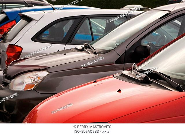 Cropped row of small cars in parking lot