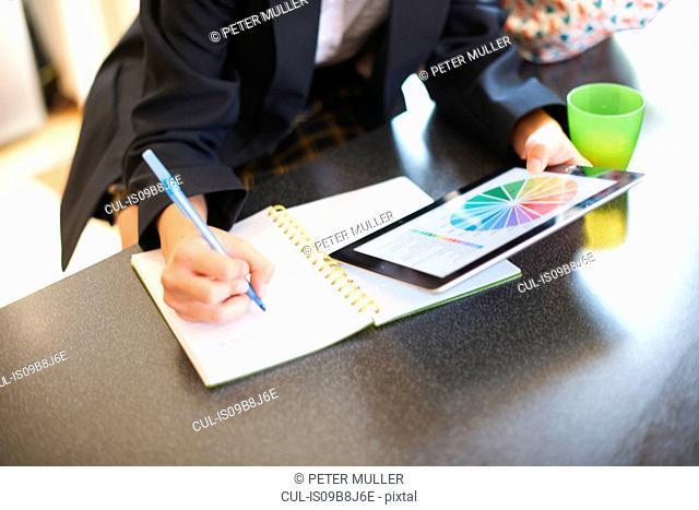 Mid section of teenage schoolgirl doing homework at kitchen counter