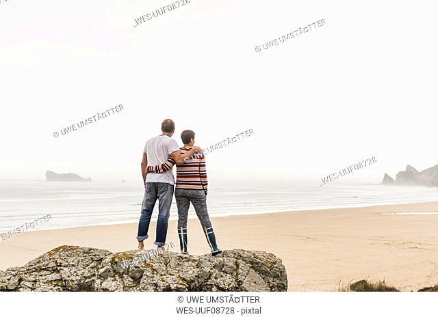 France, Bretagne, Crozon peninsula, couple standing on rock at the beach