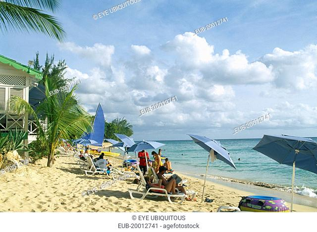 Mullins Bay. People on loungers with blue sun umbrellas on sandy beach at the waters edge with palm tree and partly seen green and white building on wooden...