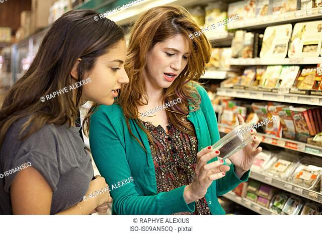 Female shoppers checking product in health food store