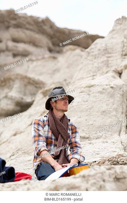 Caucasian hiker sitting on rock formation in desert