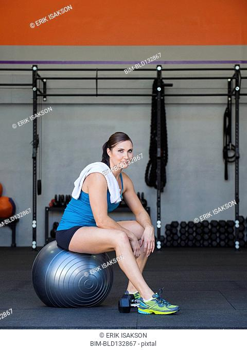Caucasian woman siting on exercise ball in gym