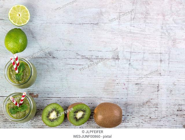 Two glasses of green smoothie and ingredients in a row on wood