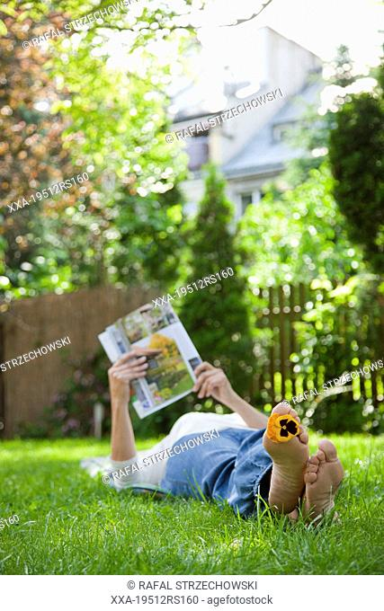Woman relaxing on grass and reading magazine
