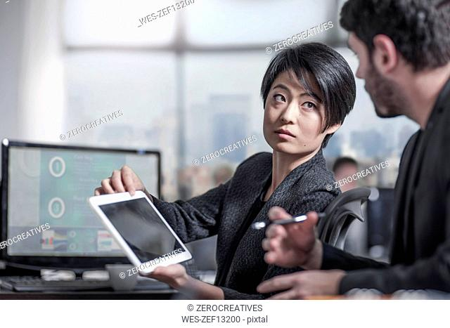 Woman showing tablet to colleauge in city office