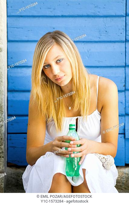 Pretty young blonde with a bottle of water in hands