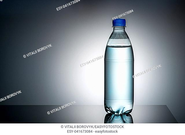 Plastic bottle with water. Gradient background. Mirror reflection